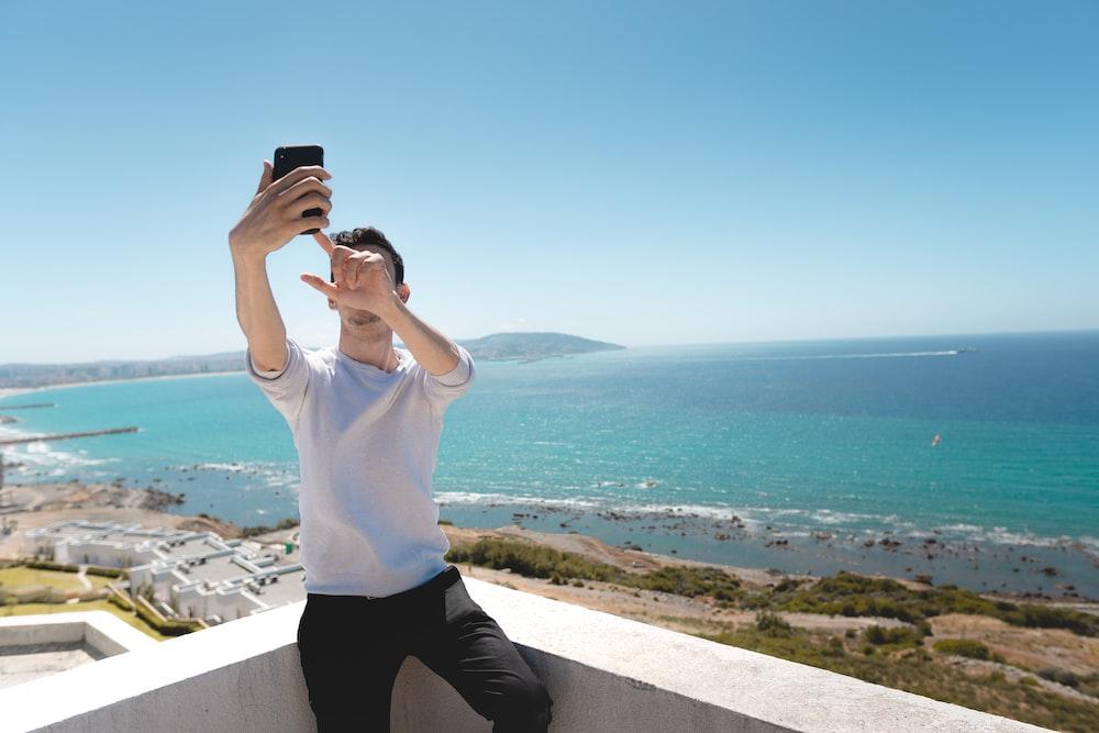 man with smartphone taking self-portrait in balcony overlooking sea