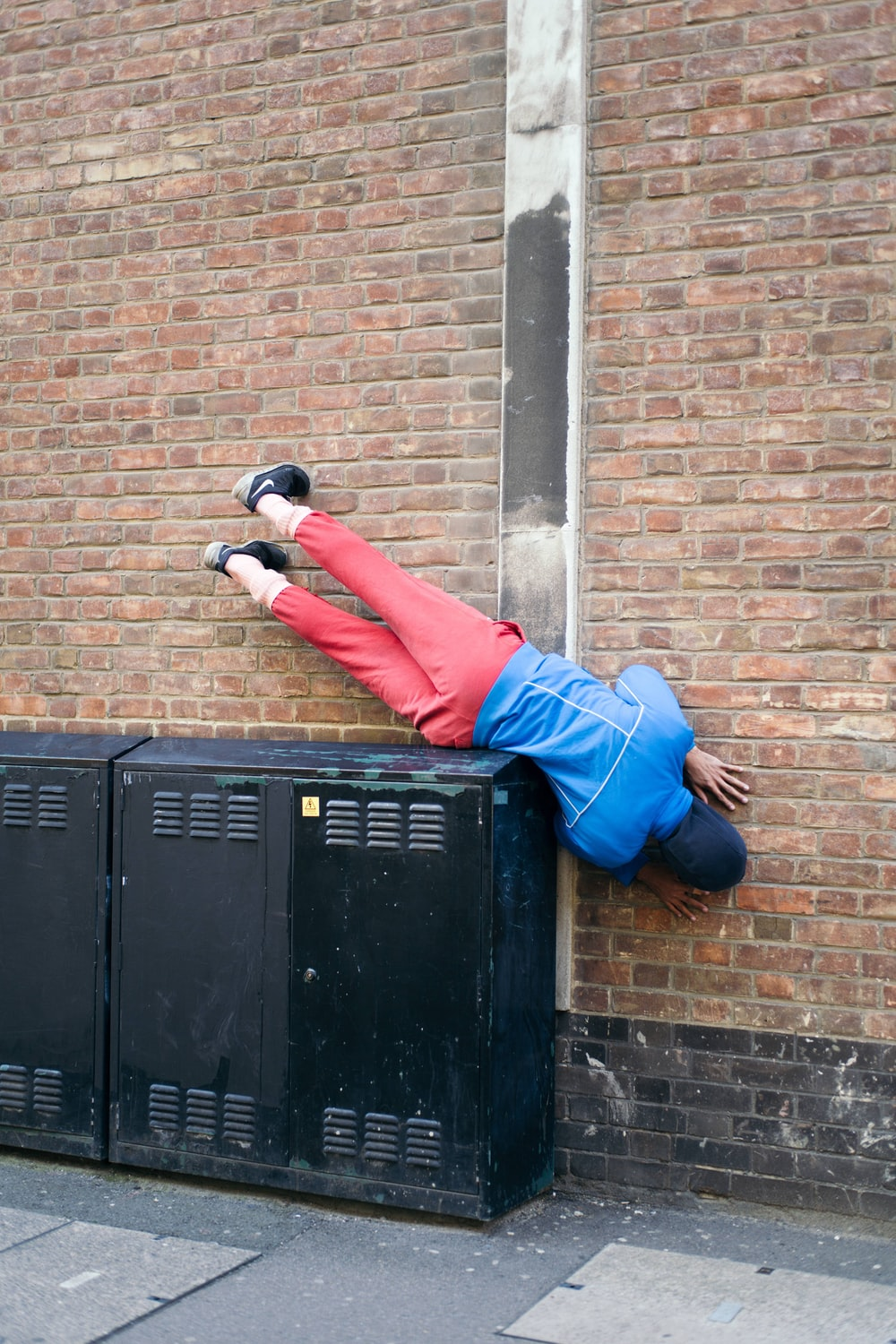 man in blue jacket and red pants lying on metal cabinet beside wall
