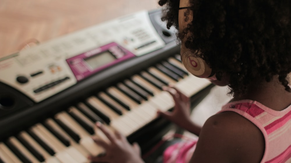 girl playing white and black electronic keyboard