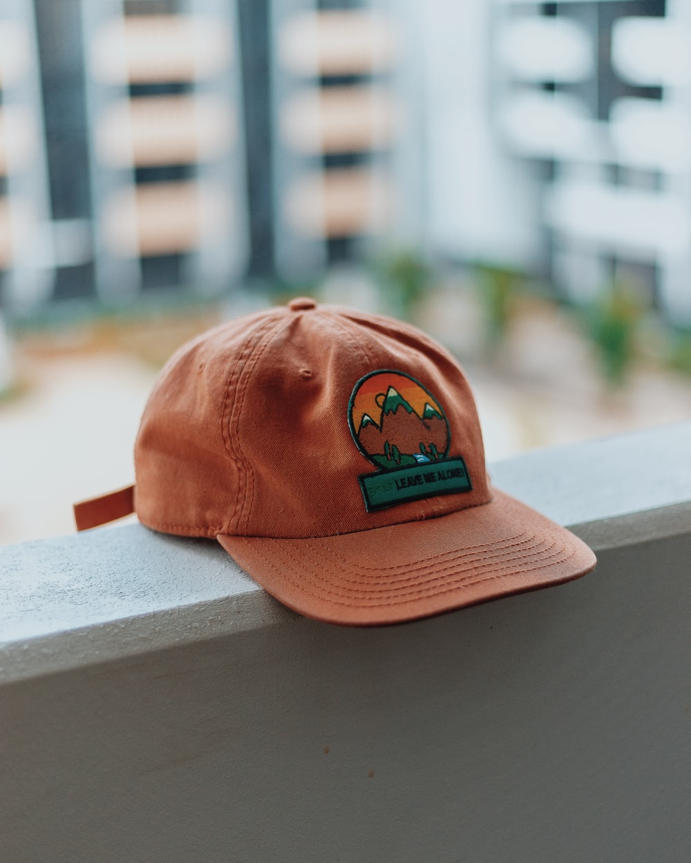 orange and green mountain embroidered cap on pavement