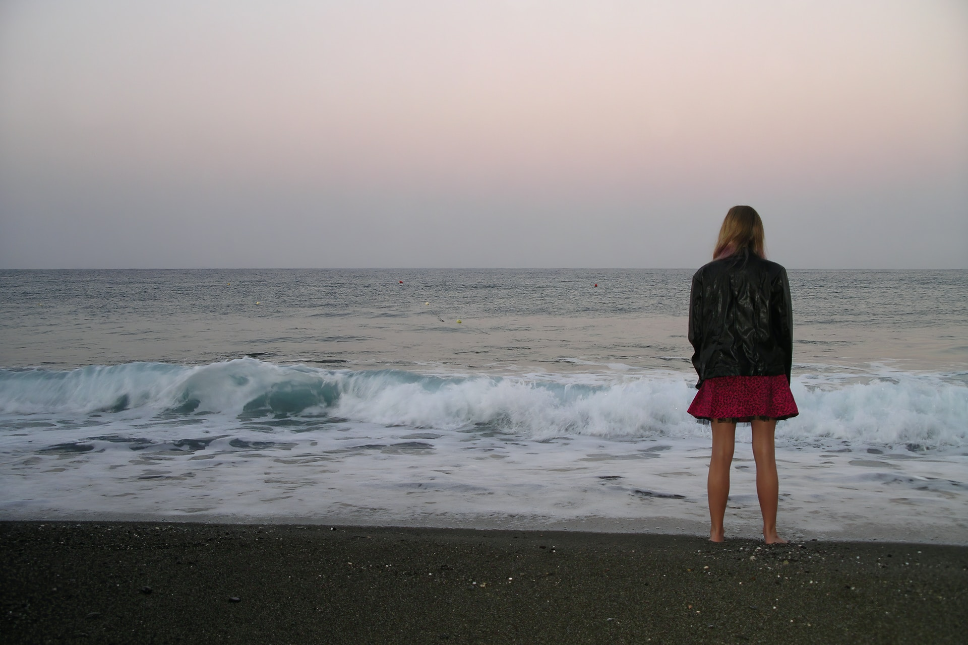 woman standing on shore looking at sea