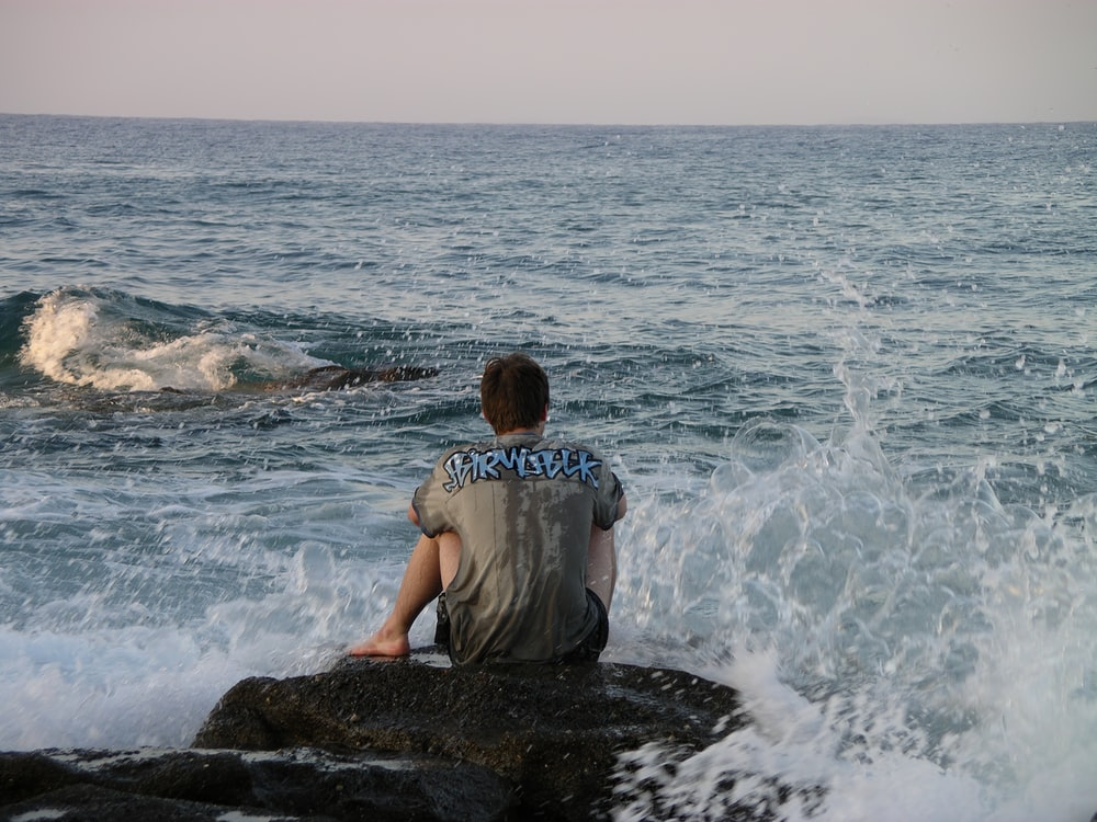 man sitting on rock in beach