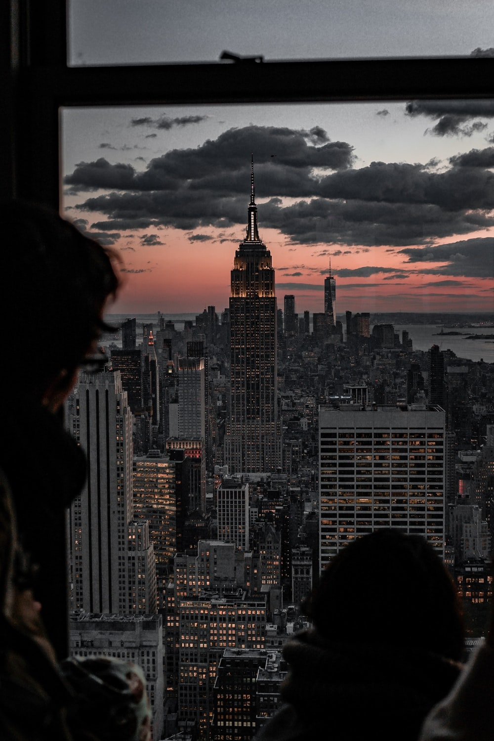 person looking at Empire State Building from glass window at dusk