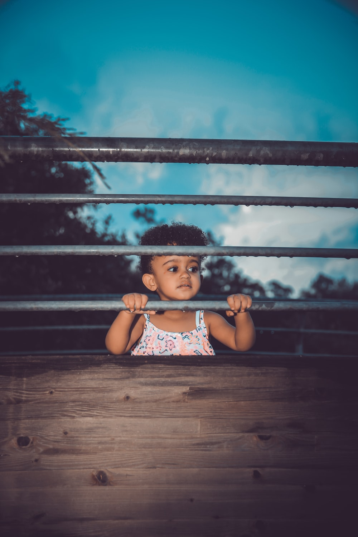 フェンスの横に立っている女の子