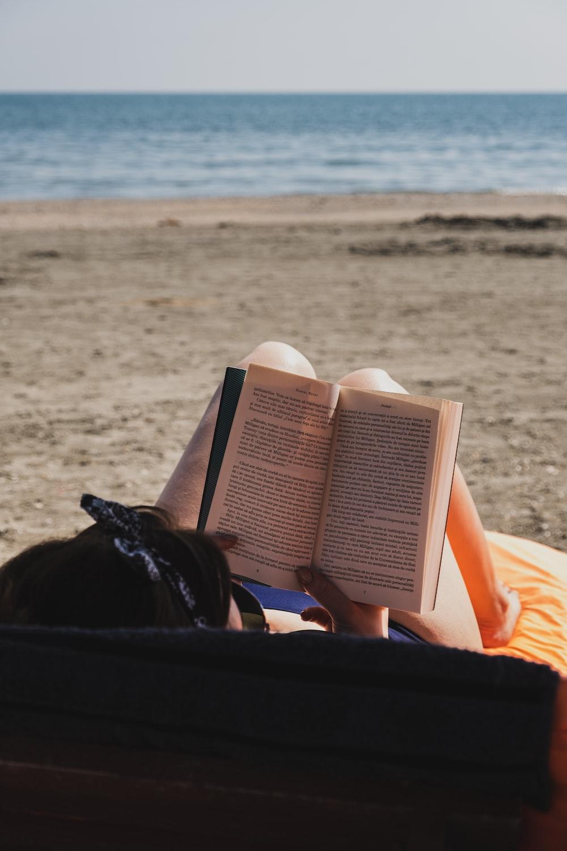 woman reading book beside beach