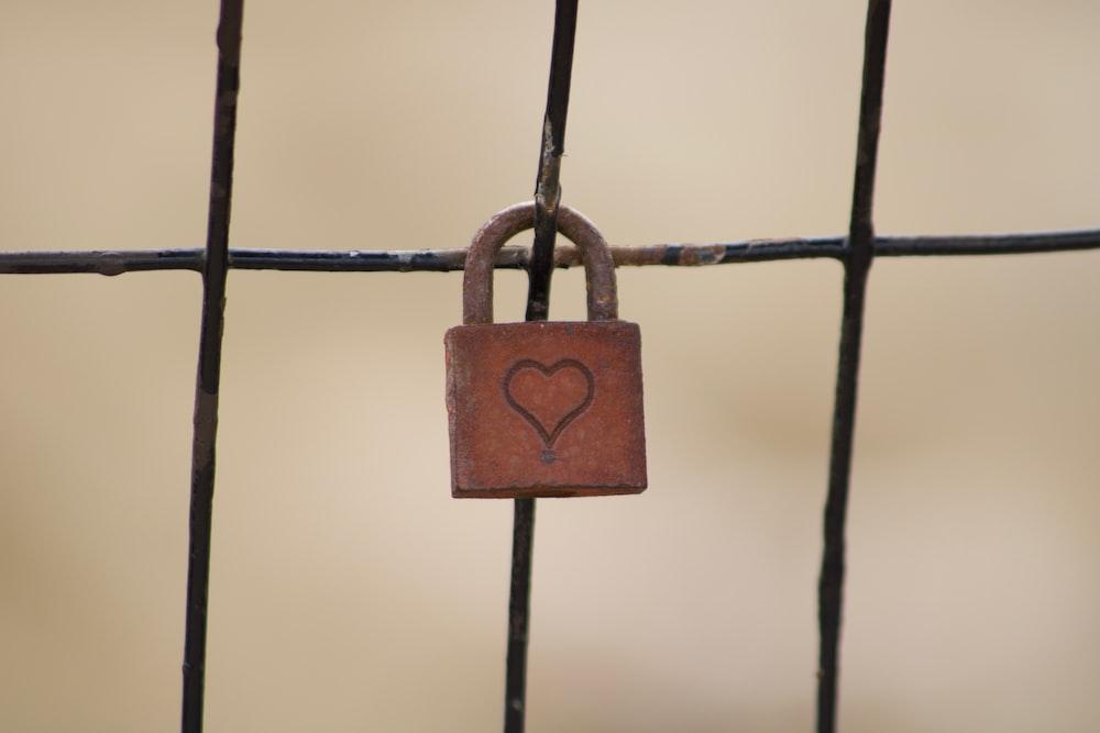brown padlock on gray fence