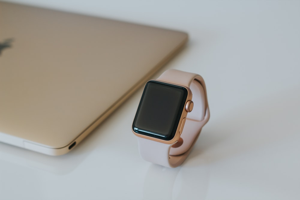 gold Apple Watch with white Sport Band