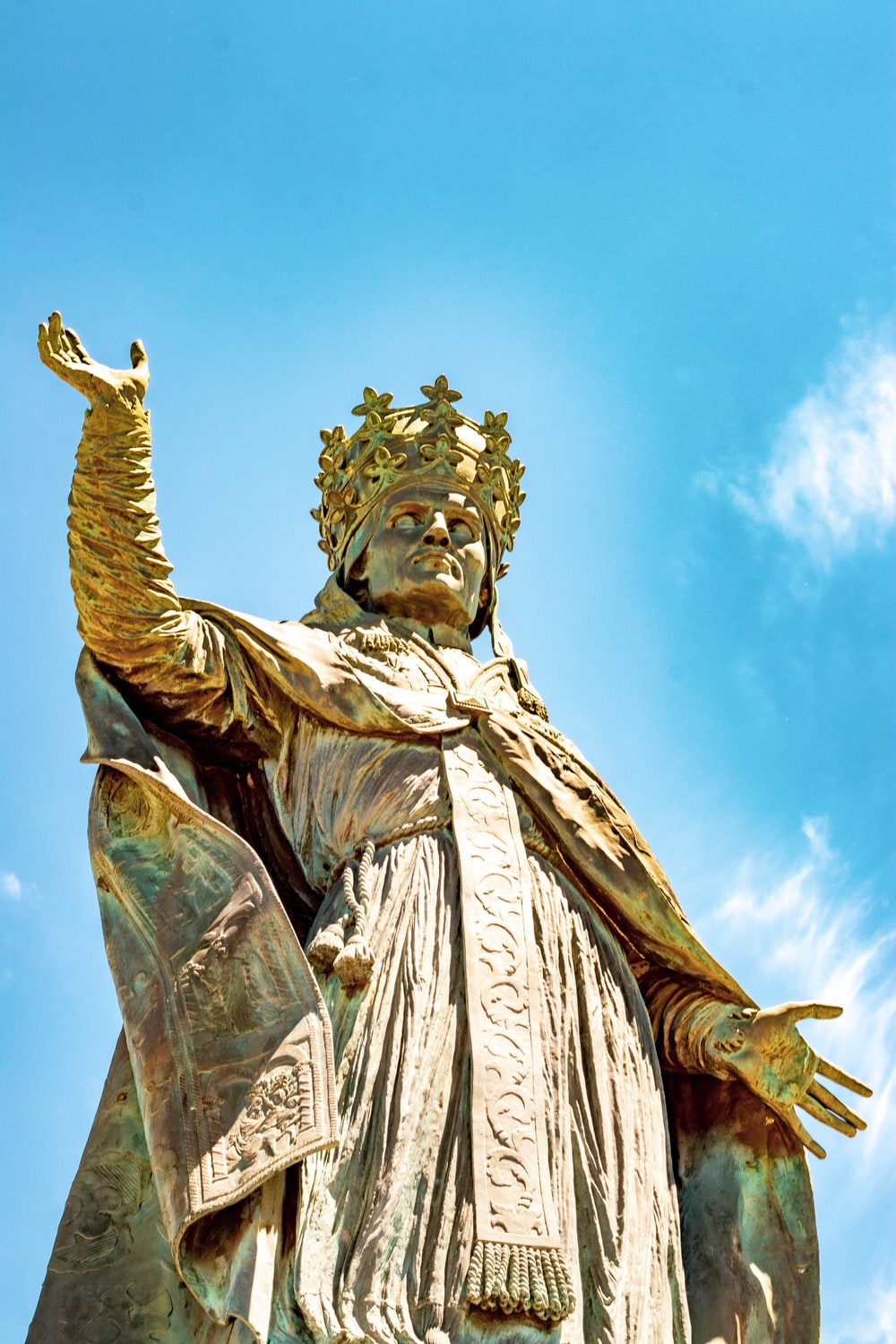 close-up photography of man wearing cape and crown statue during daytime