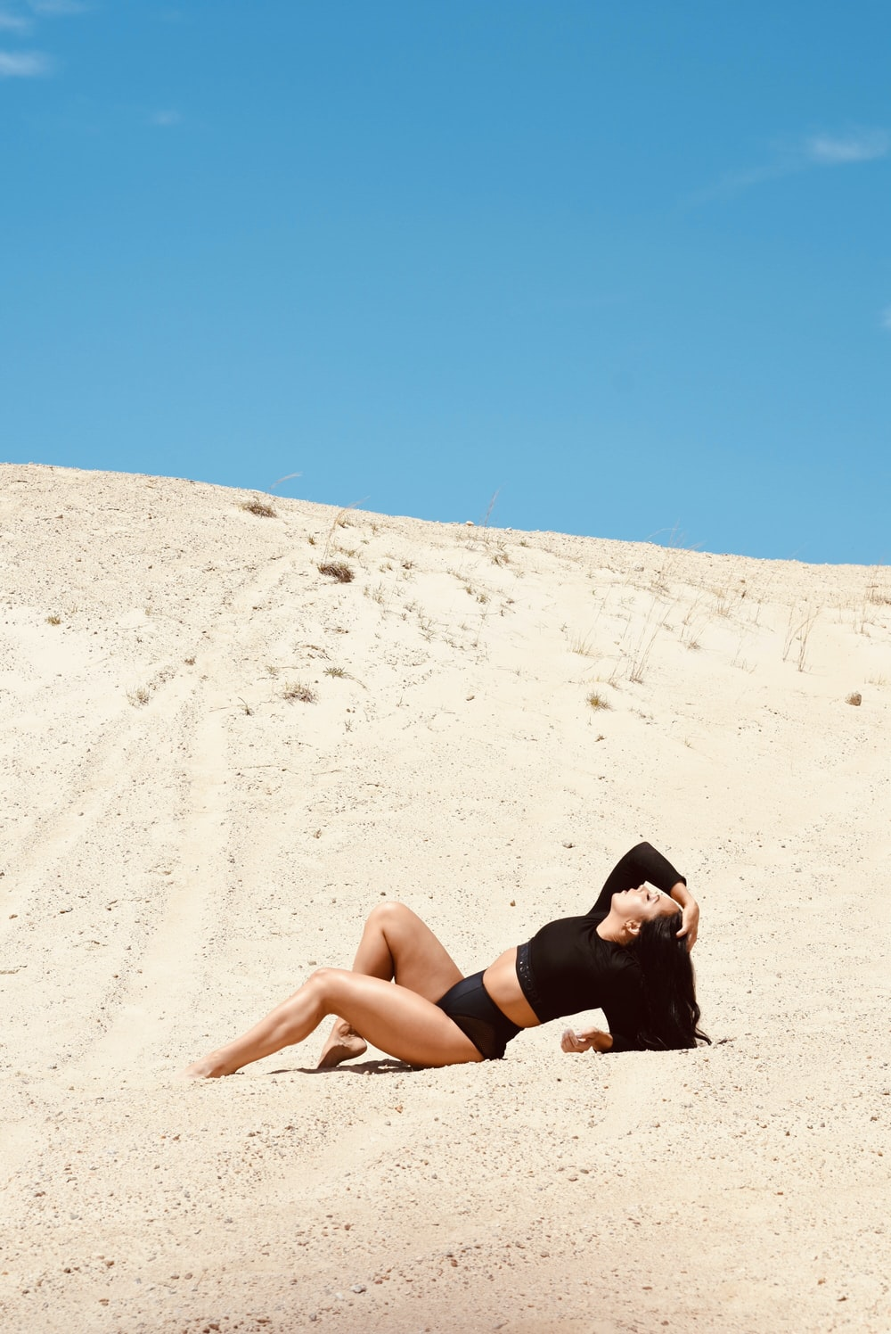 woman lying on brown sand during daytime