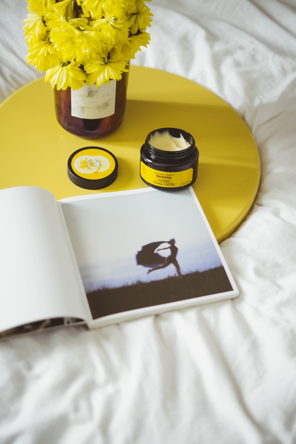 white book and round black container on top of yellow tray