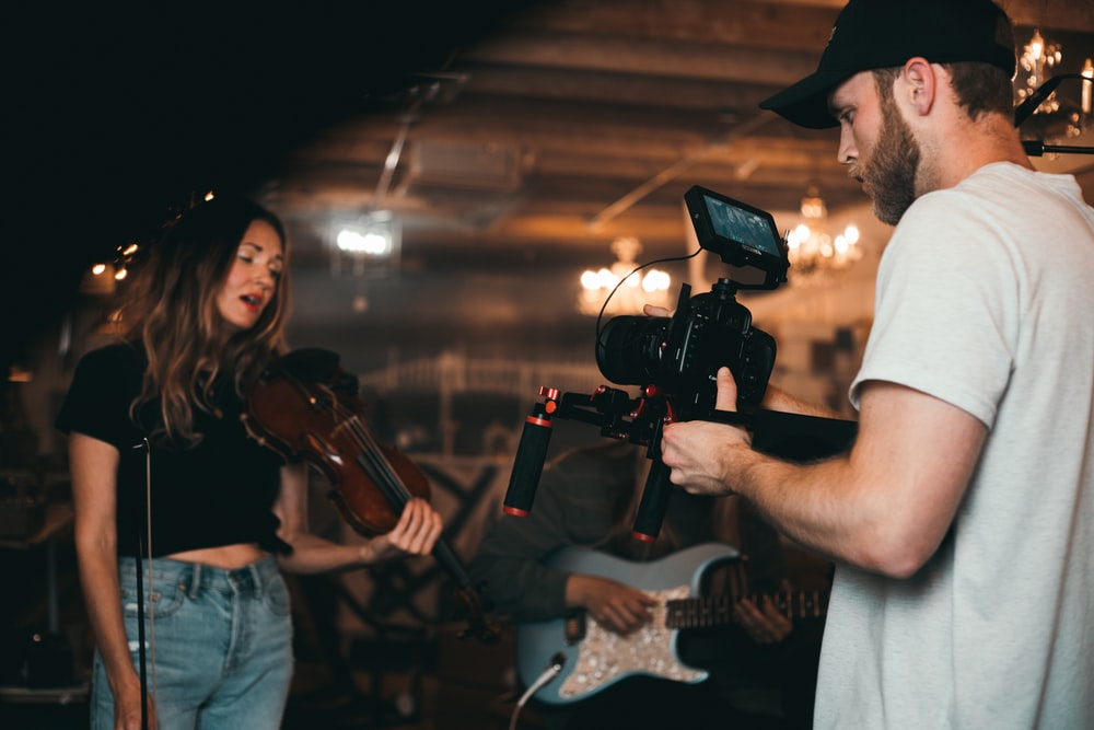 man taking video of woman holding violin