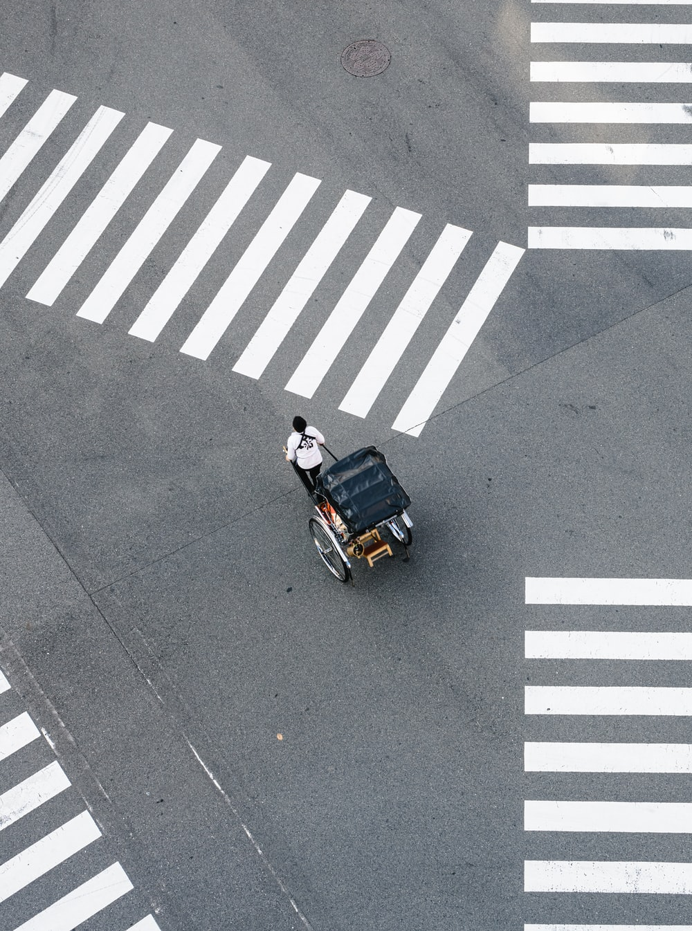 man pulling carriage crossing pedestrian