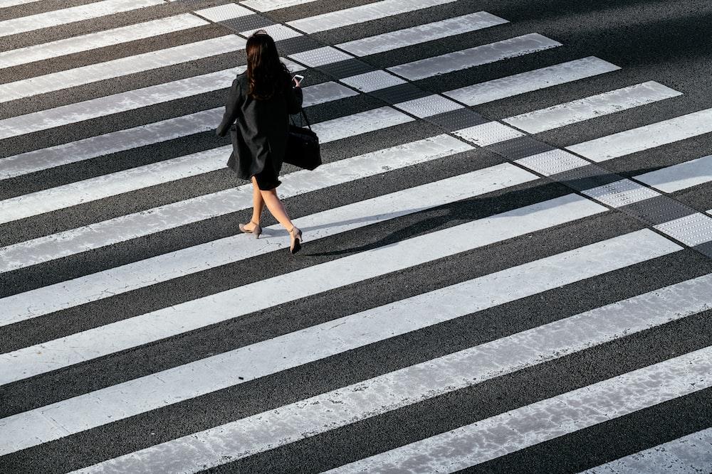 woman in black coat crossing pedestrian
