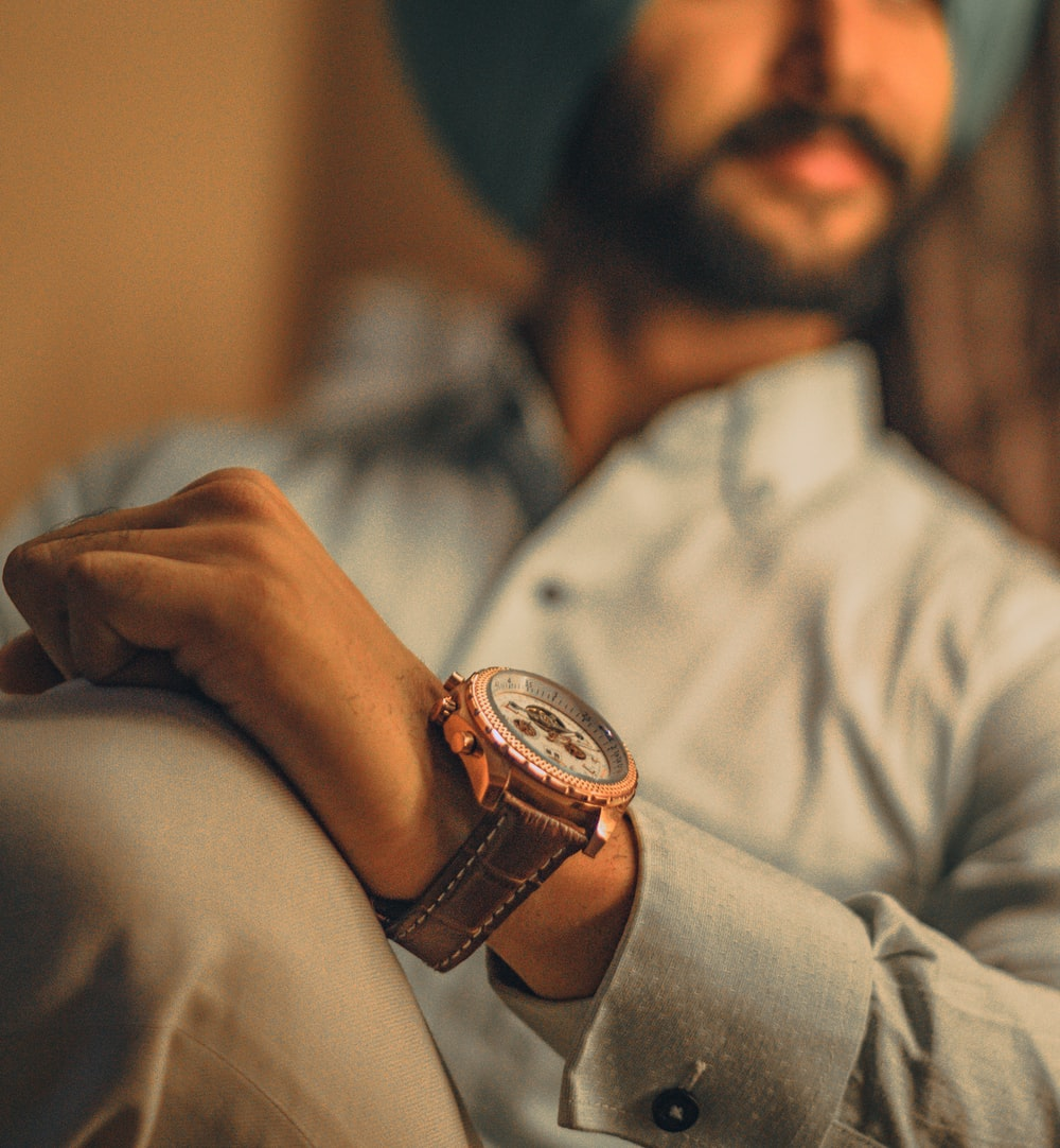 shallow focus photo of man wearing round gold-colored chronograph watch with brown leather strap