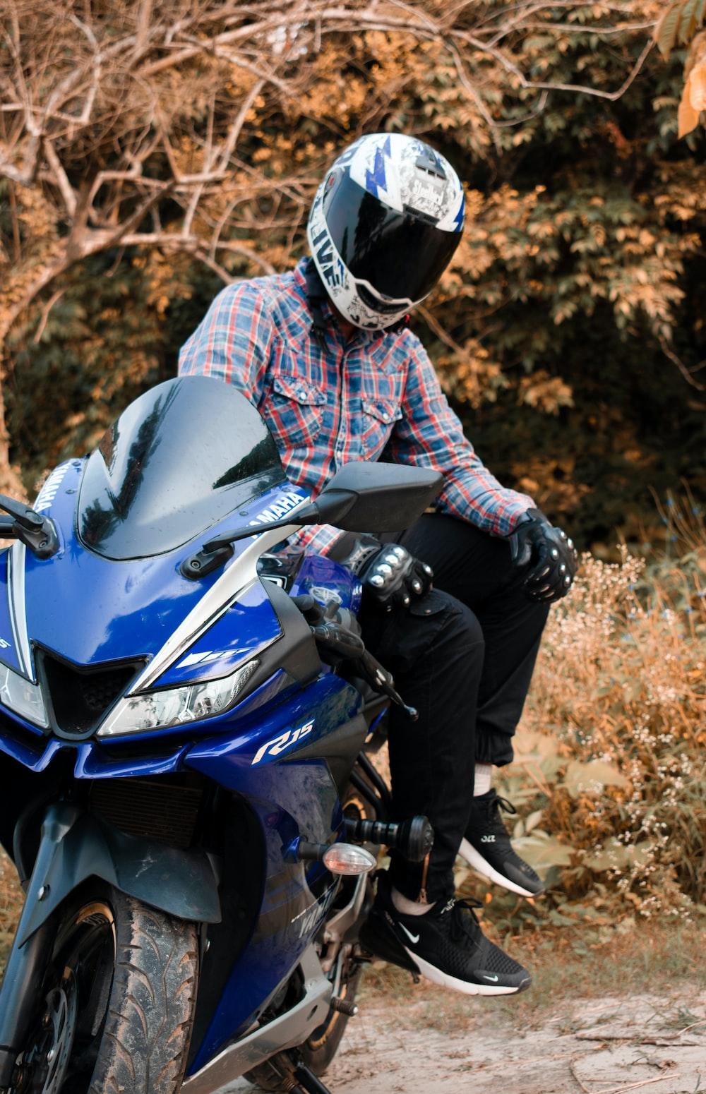 man wearing white helmet sitting on blue sports bike
