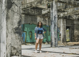 woman in blue shirt, blue plaid blazer and blue denim shorts standing in front of graffiti painted wall