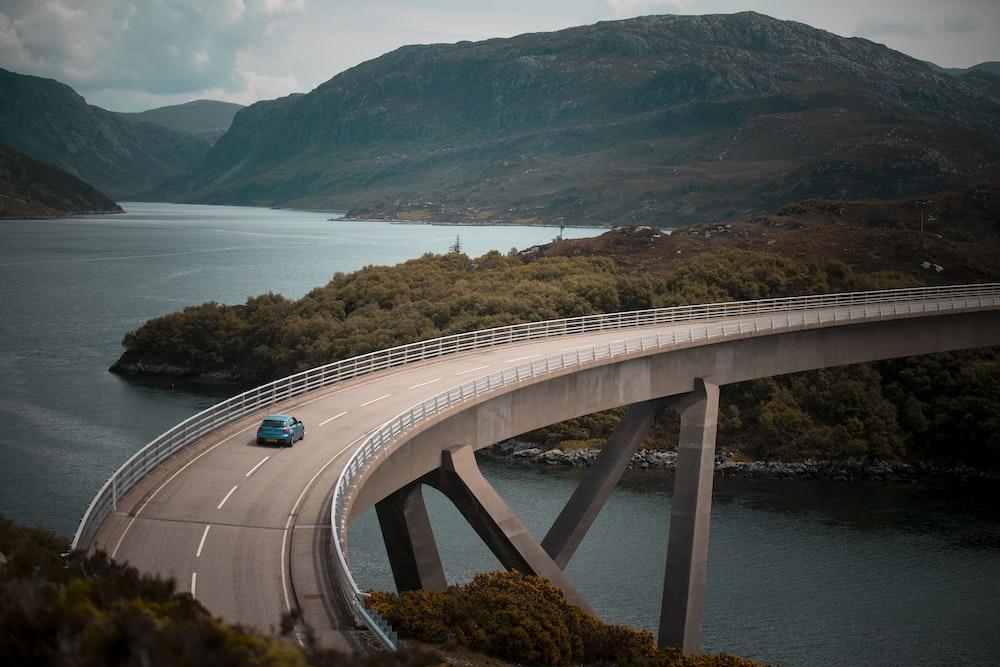 blue vehicle driving on bridge during daytime