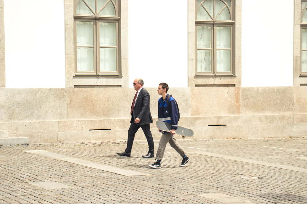 two men walking beside white concrete building
