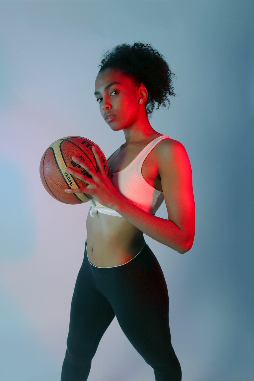 standing woman wearing pink sports bra holding basketball