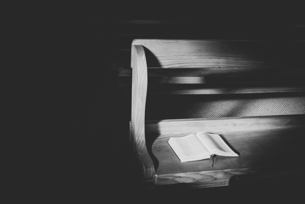 grayscale photo of open book on bench