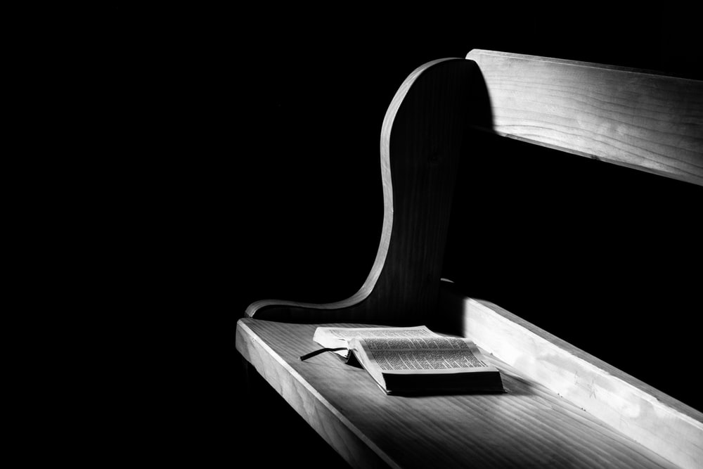 book opened on brown wooden pew