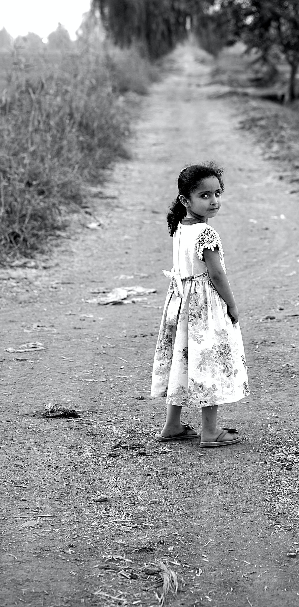 girl standing in the middle of dirt road during day