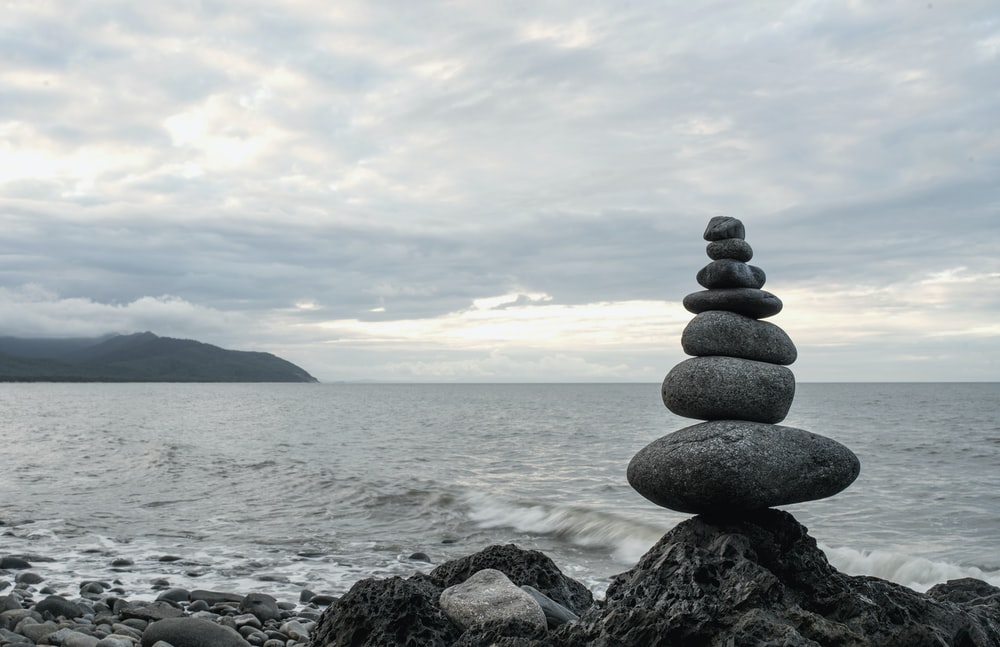 close-up photo of Cairn near seashore