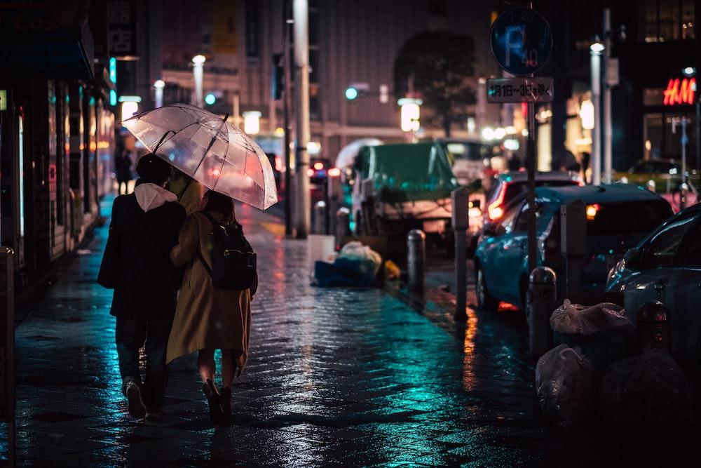 people holding umbrella walking on wet road