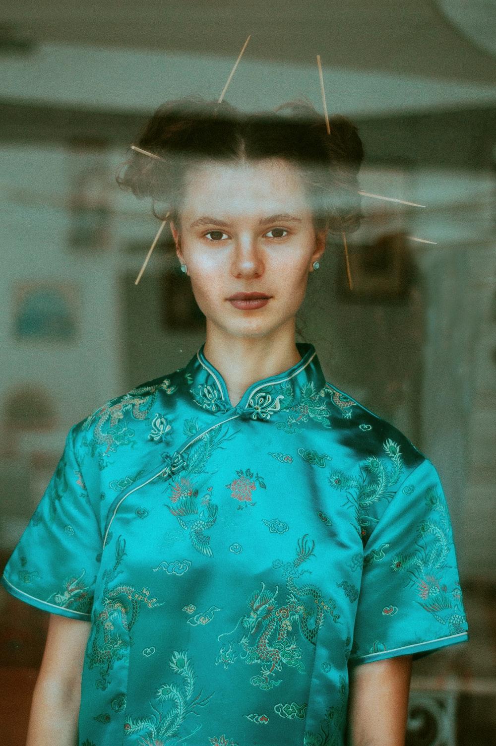 woman wearing green short-sleeved top inside room