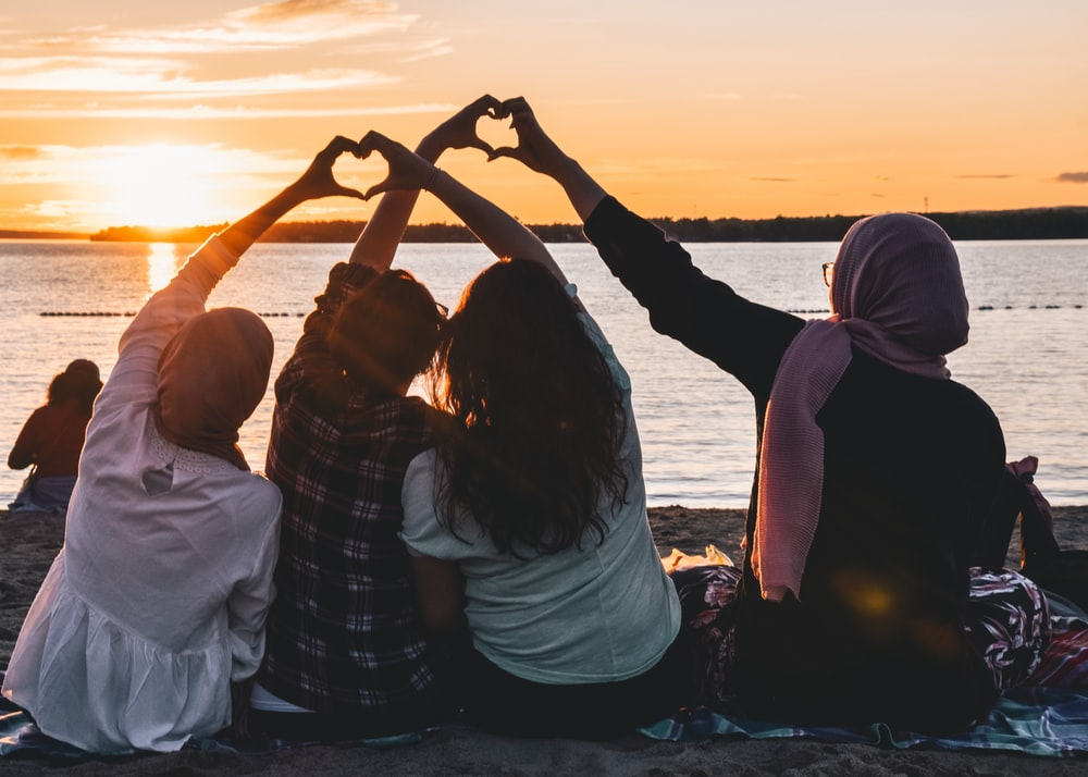 four people sitting on shore forming hearts with their hands during golden hour