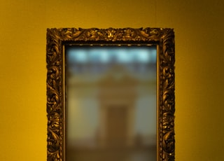 rectangular leaning mirror with brass-colored frame
