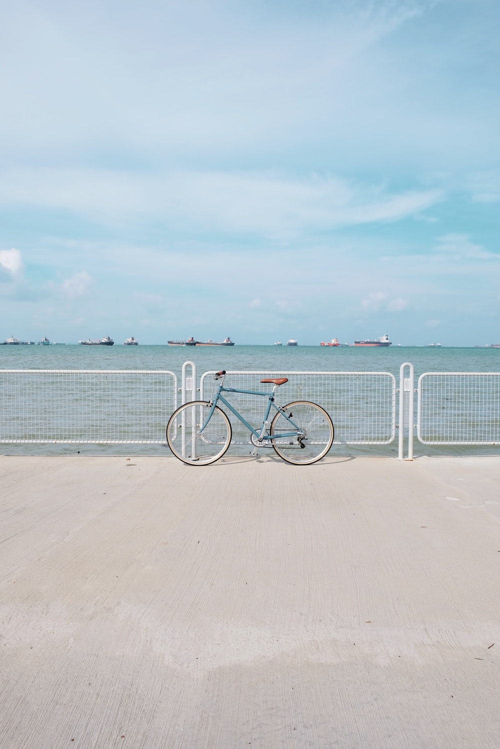 blue commuter retro bike leaning on dock railing