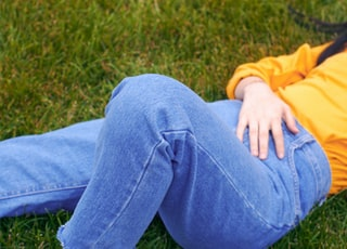 person lying on green grass wearing blue denim jeans