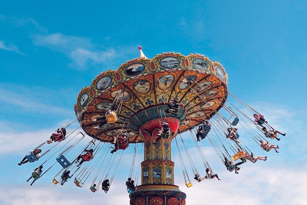 people rides on carousel during daytime