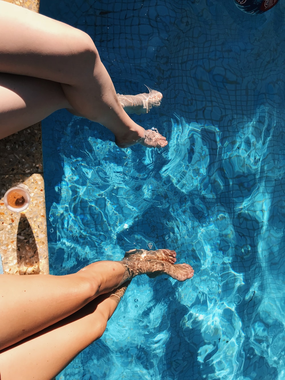 two women's feet in the pool