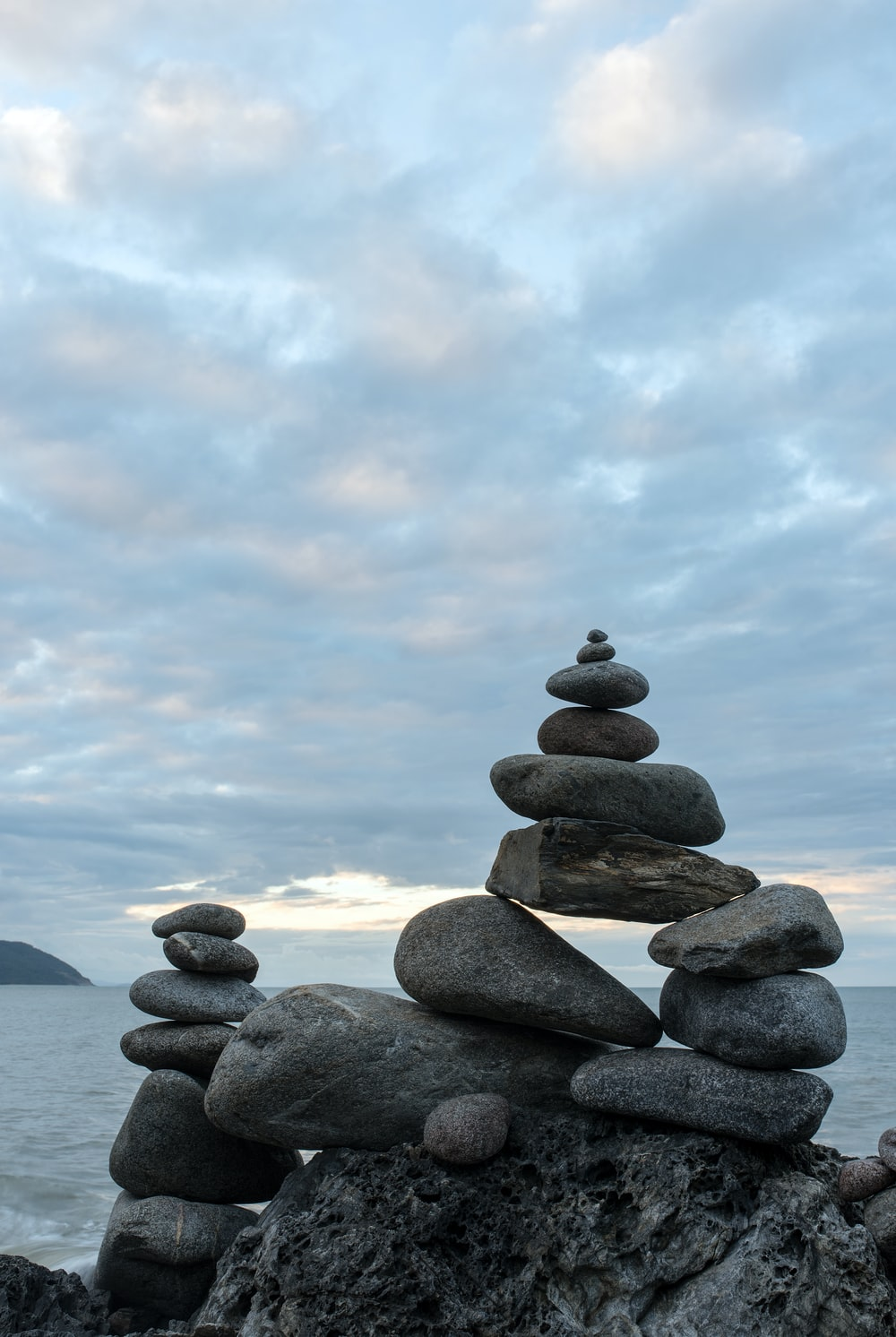 balanced stones on rock beside the ocean