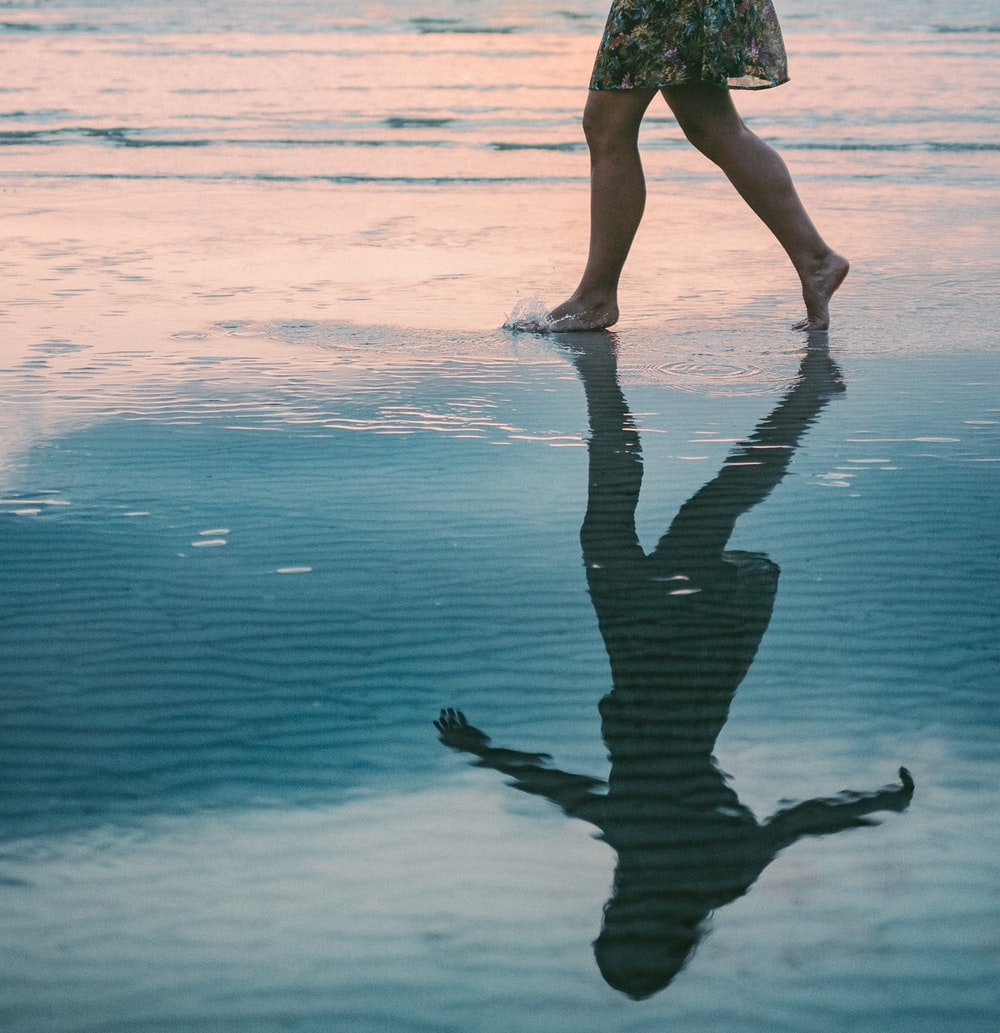 woman walking on body of water beside shore during daytime