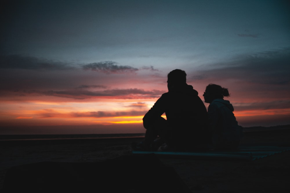 two person sitting during golden hour
