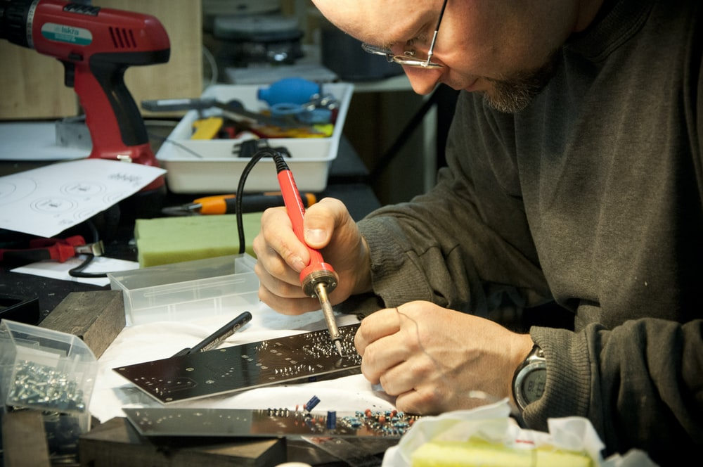 man fixing the device using soldering iron