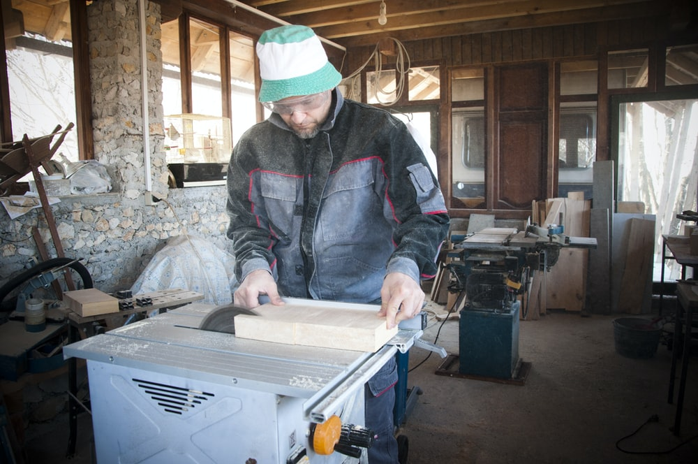 person wearing black and gray jacket cutting wooden board on table saw