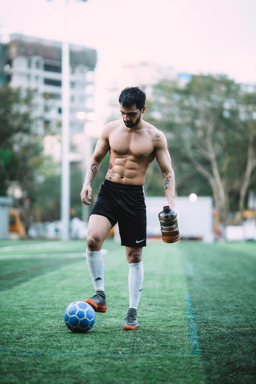 man playing soccer ball during daytime