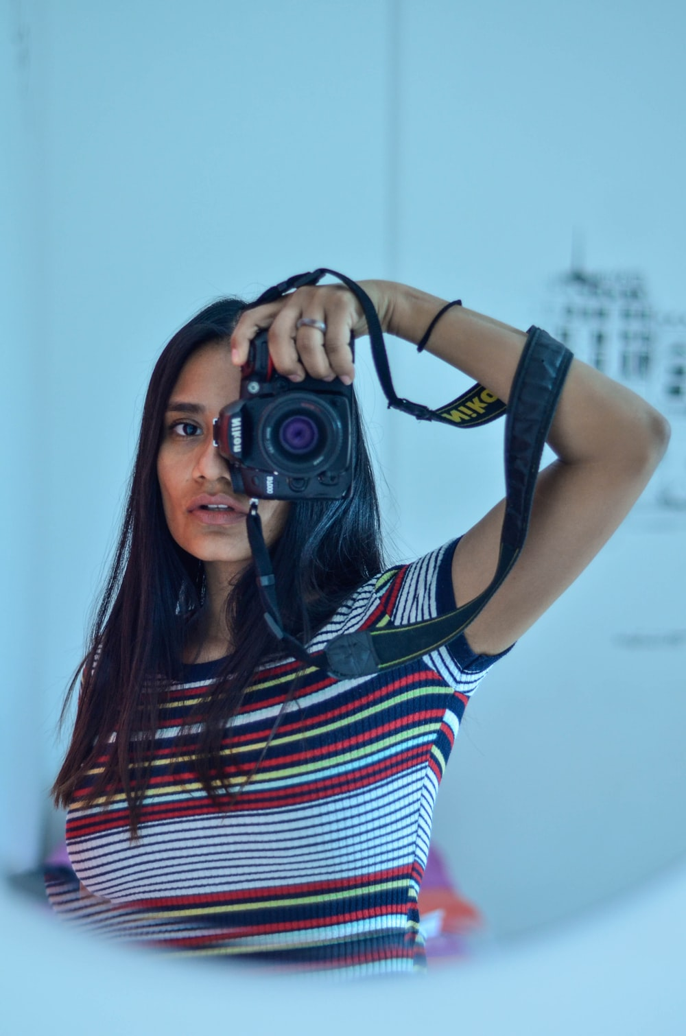woman in striped t-shirt holding camera