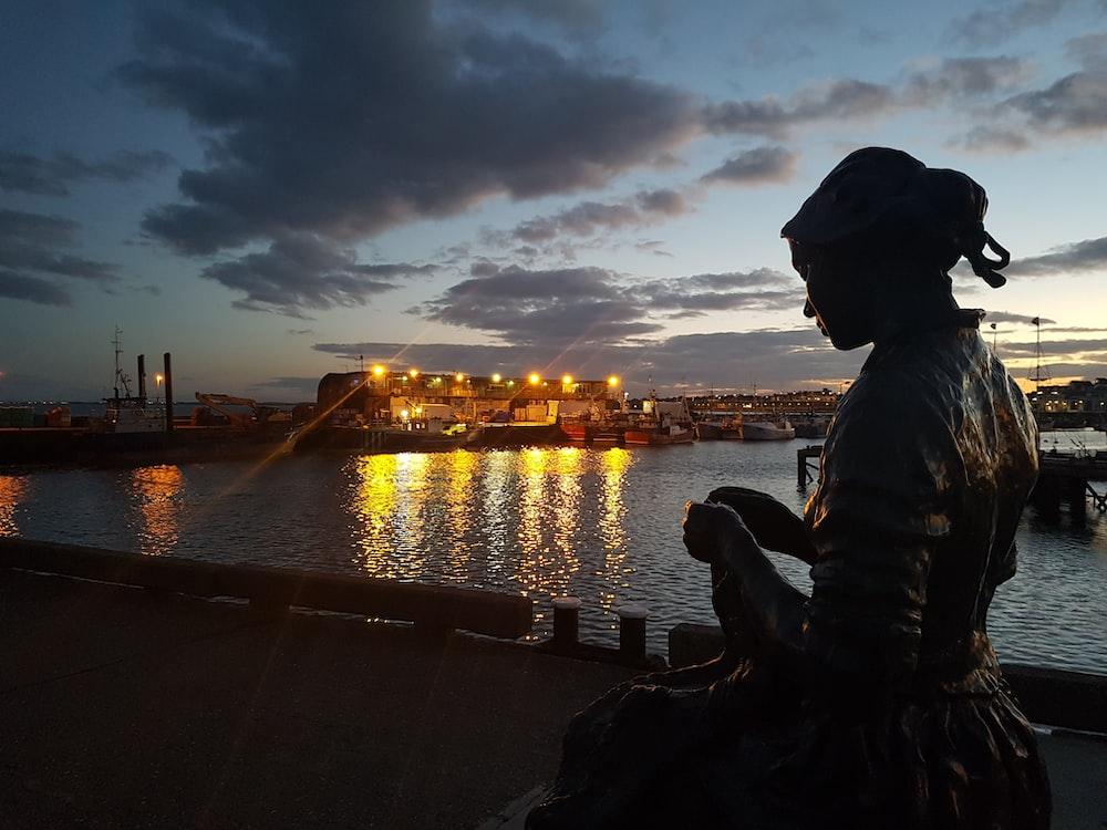 silhouette of woman in dress near dock
