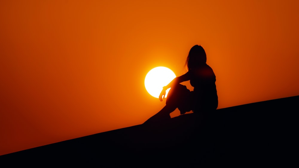 silhouette of woman sitting on ground