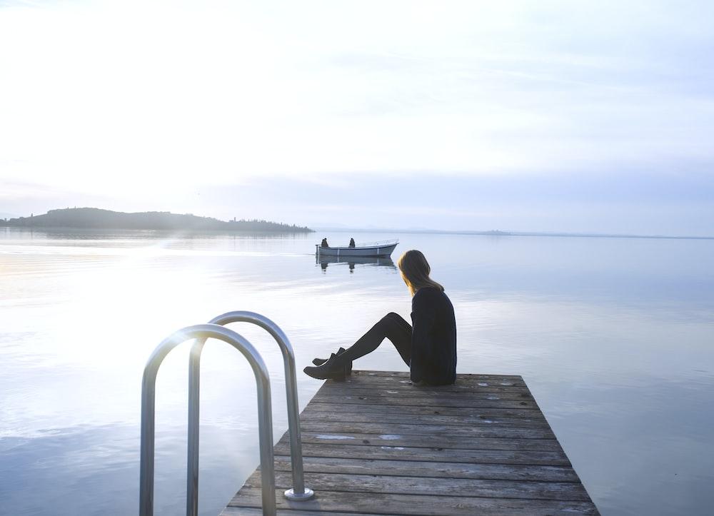 woman sitting on wooden dock near boat