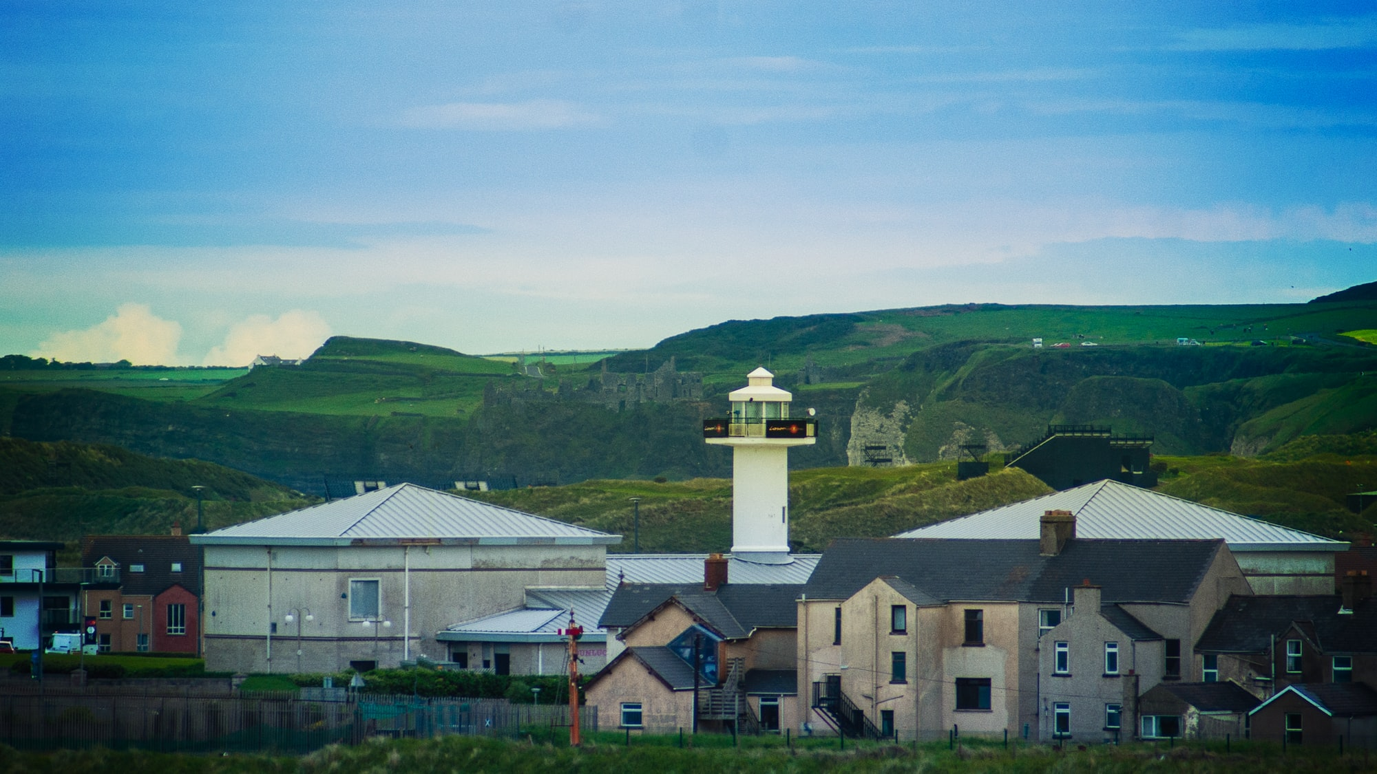 The lighthouse at Portrush with the stands for the Irish Open Golf Tournament and the ruins of Dunluce Castle in the background.