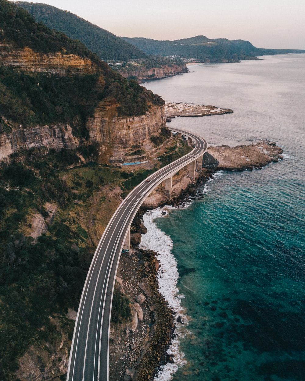 aerial photography of road beside sea