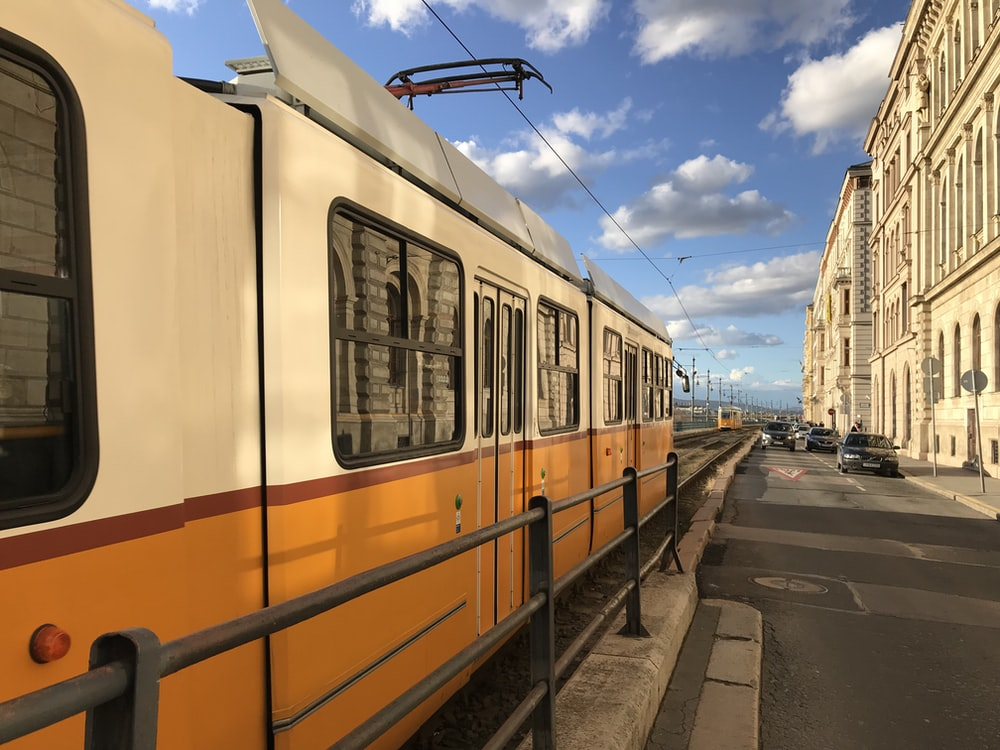 white and orange train in front of building