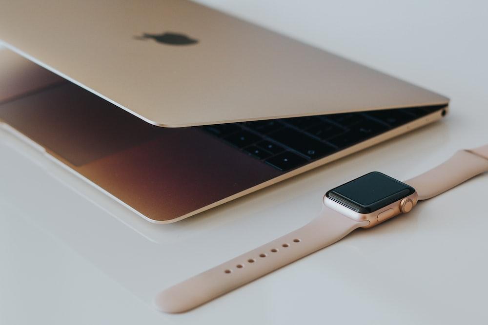 gold case Apple watch beside silver MacBook