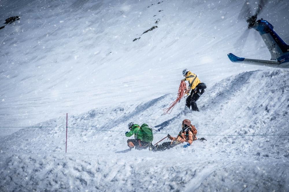 three person on snow covered aera